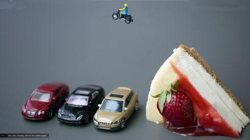 Christopher Boffoli's photograph of a toy motorcycle rider, jumping over three toy cars and a slice of cheesecake