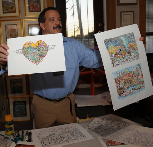 Image of a man named Jaime holding up posters of Charles Fazzino's paintings at ArtsFest