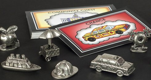 New York Edition of Monopoly pieces, including a dancing bagel, apple, Staten Island ferry, hot dog cart, NYFD helmet, and NY taxi cab
