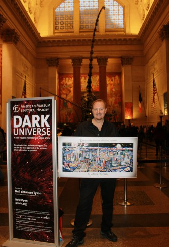 Charles Fazzino standing in the Museum of Natural History proudly holding one of his posters