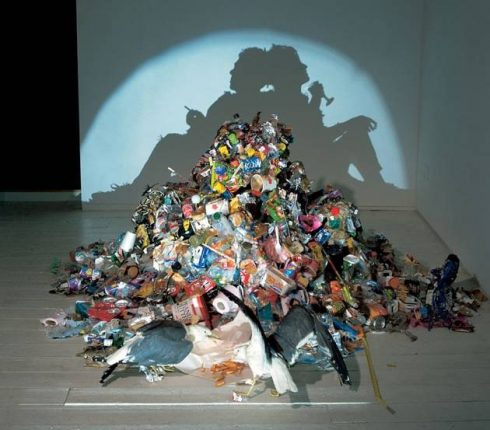 A large pile of trash lends to a shadow of two people sitting back to back leaning on each other