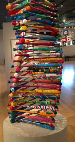 Image of a large sculpture constructed of colorfully painted baseball bats stacked up into a large 3D triangular shape.