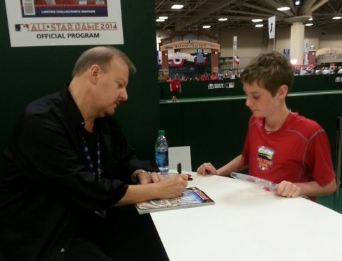 Charles Fazzino sitting at a table at the MLB All Star Fan Fest signing a program for a young boy.