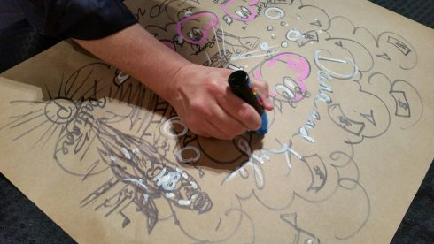 Charles Fazzino hand doodling a piece for a client on cardboard