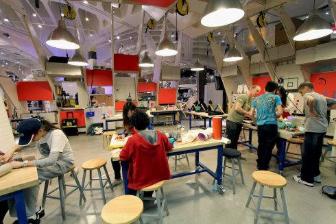 Children and teens gathered around tables creating and building things inside a makerspace.