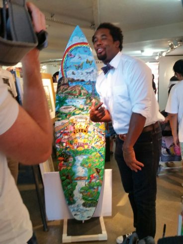 NBC's, Dhani Jones, stopped The USA house to admire Charles Fazzino's 2016 Olympic Games surfboard in Rio.