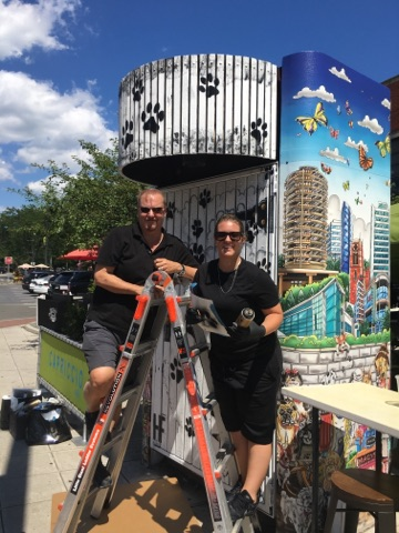 Charles and Heather Fazzino standing on an orange ladder in front of their latest pop-art piece, Downtown Dogs in Stamford