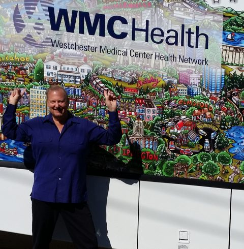 Charles Fazzino, in a blue button down, in front of the Westchester Medical Center Health Network Pop-Art bus