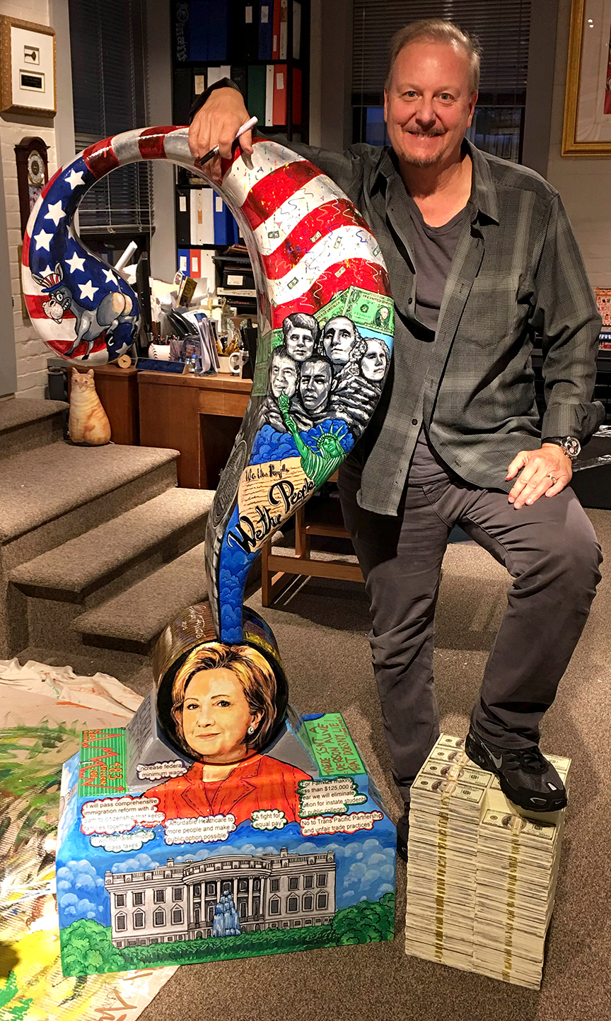 Charles Fazzino standing next to his Hilary Clinton question mark sculpture dedicated to the 2016 presidential debate