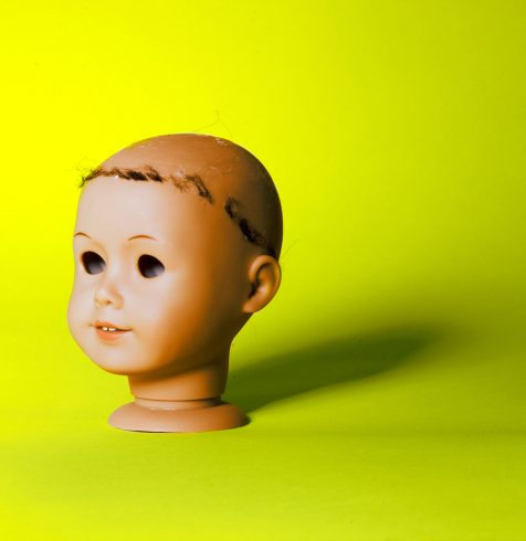 A photo of a doll head with a neon yellow background shot by photographer Nicholas Rouke