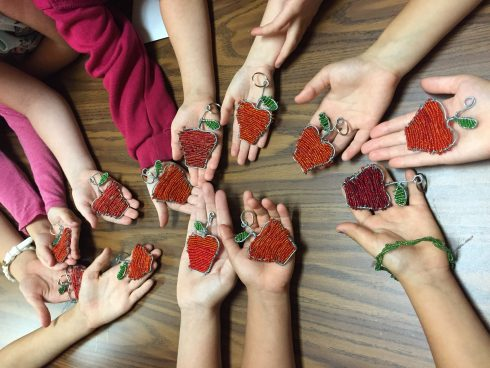 Childrens hands holding Fazzino inspired art project at the Kids Need More Art studio