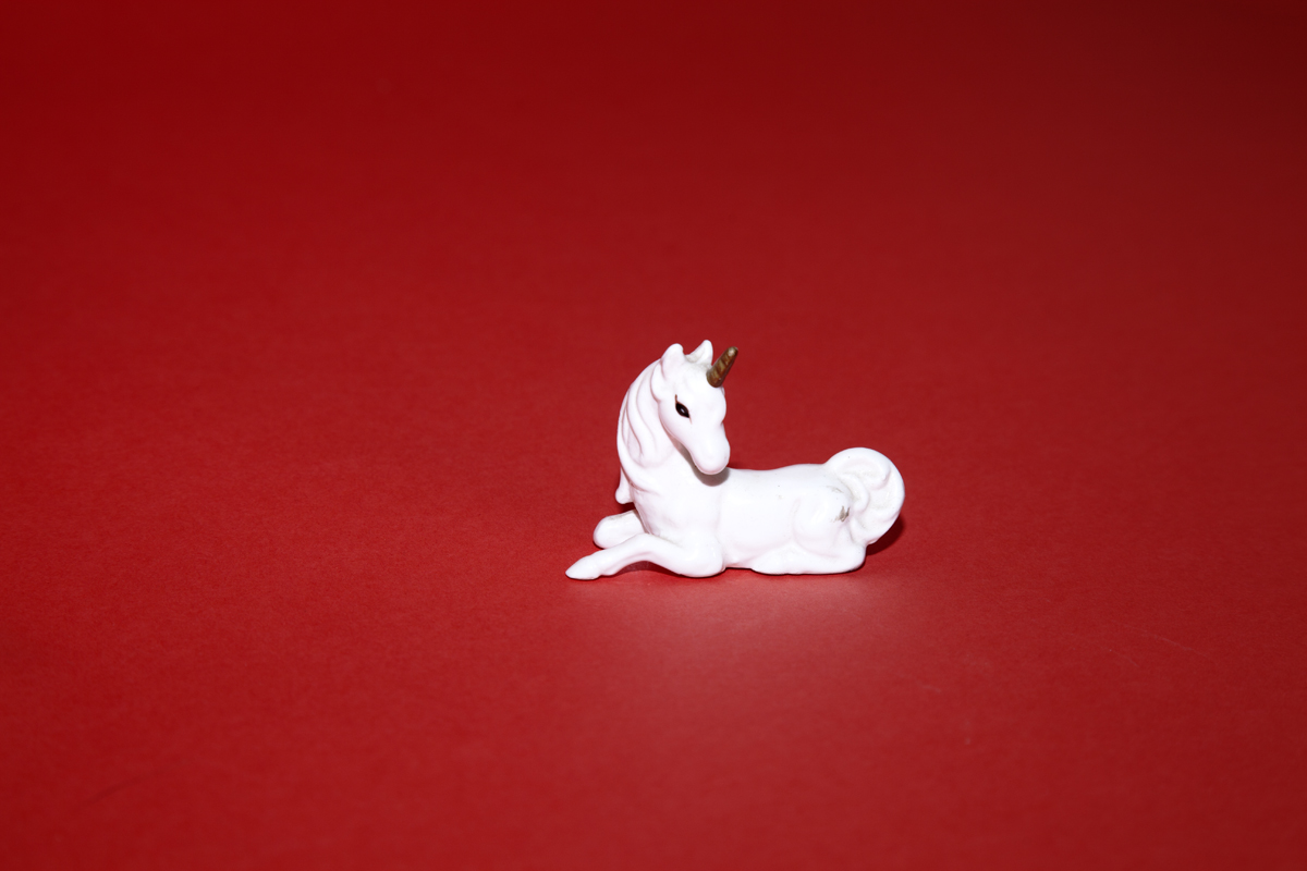 White unicorn shot on a red background shot by photographer Nicholas Rouke