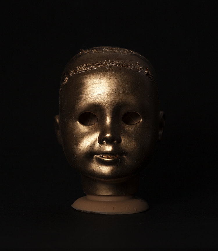 Gold painted doll head on a black backdrop shot by photographer Nicholas Rouke