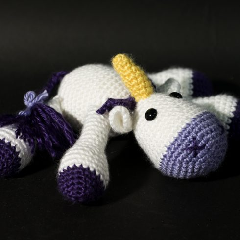 White and purple crocheted unicorn laying down | Christina's Crocheted Characters
