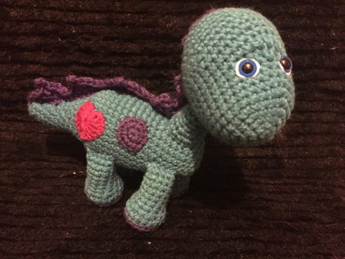 A green and maroon crocheted dinosaur with a red heart | Christina's Crocheted Characters