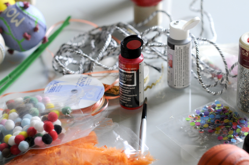 A table full of craft supplies like pom poms, paint, brushes, ribbons for making baseball art