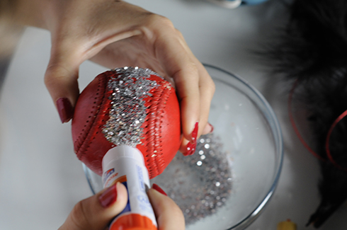 Adding glitter to a red baseball to create art
