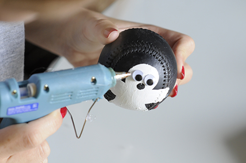 Using a heat gun to attach googly eyes for a ghost painted on a baseball