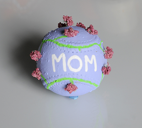 A purple painted baseball with Mom and flowers on it.