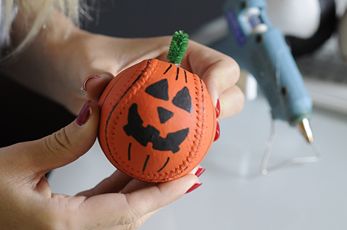 A pumpkin baseball with triangle eyes, teeth and a pipe cleaner stem
