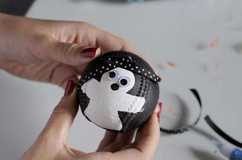 A black with white polka dot ribbon added as a bow to a ghost baseball art