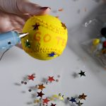 Adhering stars in different colors to a baseball to create an art piece