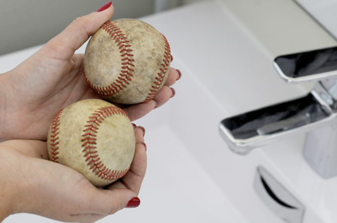 Holding two baseballs in preparation for cleaning them to create art