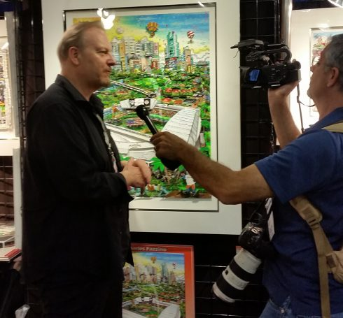 Charles Fazzino standing in front of his 2017 All-Star 3D pop art collection, being interviewed at MLB Fan Fest