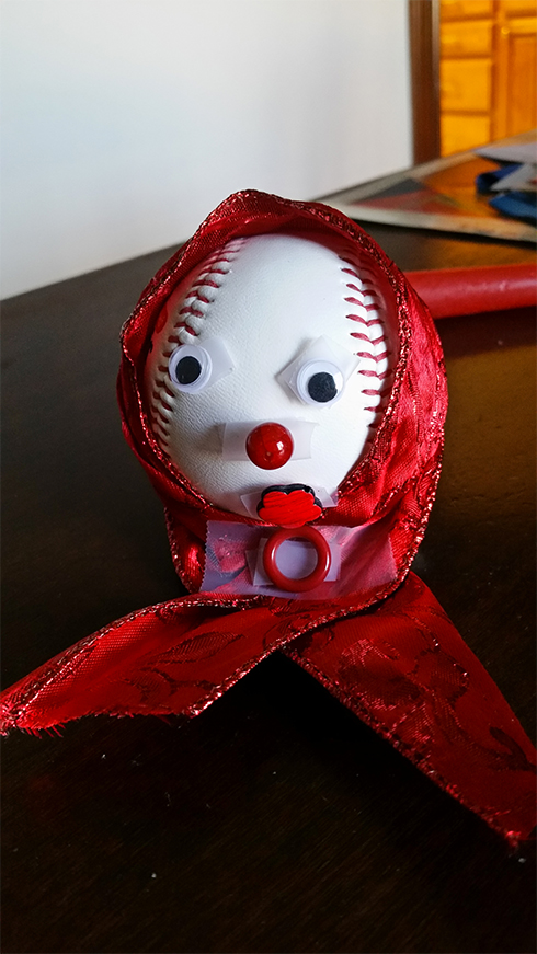 A baseball with a red cape over the head, googly eyes and a red nose looks like a grandma