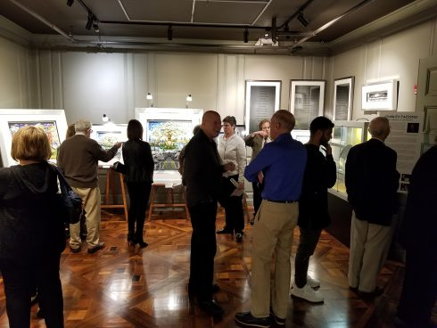 People gathered in a dim lit gallery at the Holocaust Memorial & Tolerance Center of Nassau County (HMTC) for Charles Fazzino's exhibit