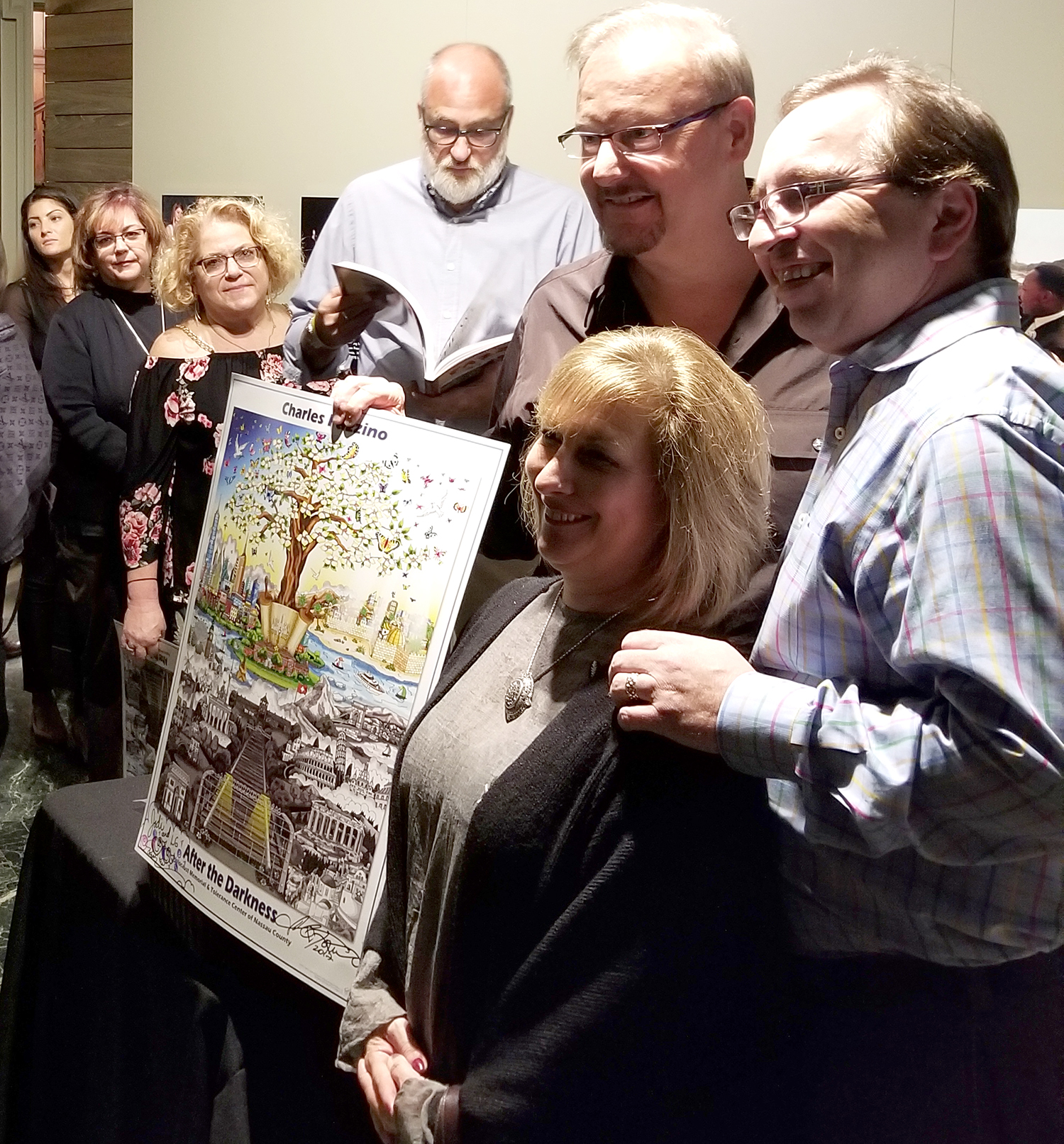 """Charles Fazzino and friends gathered to take a photo with a """"After the Darkness"""" signed pop art print"""