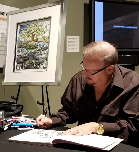 """Charles Fazzino sitting at a black table, signing books in front of his 3D Pop art piece """"After the Darkness"""" at the The Holocaust Memorial and Tolerance Center of Nassau County"""