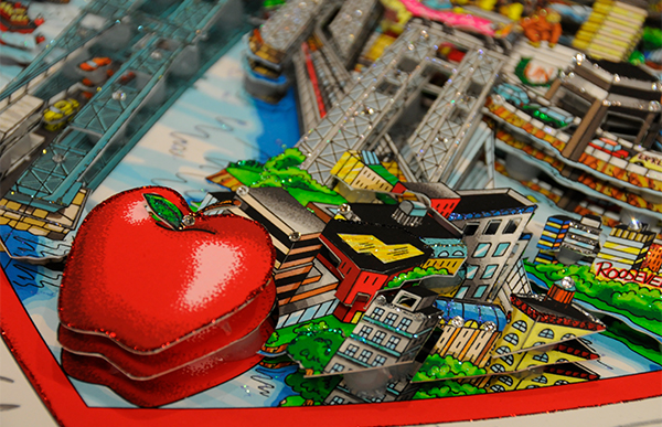 A close up of a Fazzino artwork showing an apple in 3D