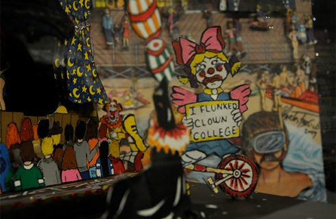 A close up of a Fazzino piece showing a clown holding a sign that says I flunked clown college