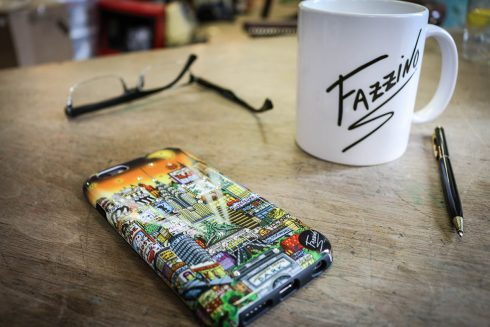 Fazzino pop art iPhone case next to a Fazzino logo mug and a pair of glasses on a wood table.