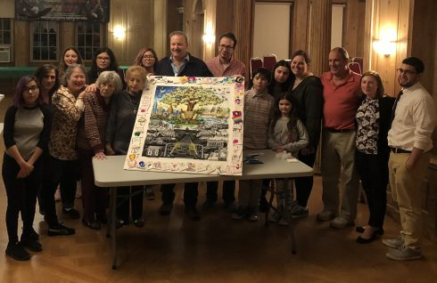 """Charles Fazzino, kids and holocaust survivors posing in front of their recreation of """"After the Darkness"""" 3D pop art piece."""