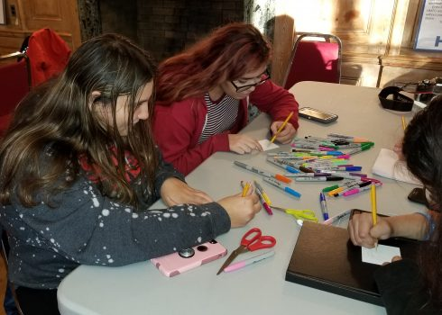 """Two young women sitting at a white fold up table, surrounded by multi-colored sharpies, using pencils to sketch out 3d pieces for Charles Fazzino's recreation of """"After the Darkness"""" pop art piece"""