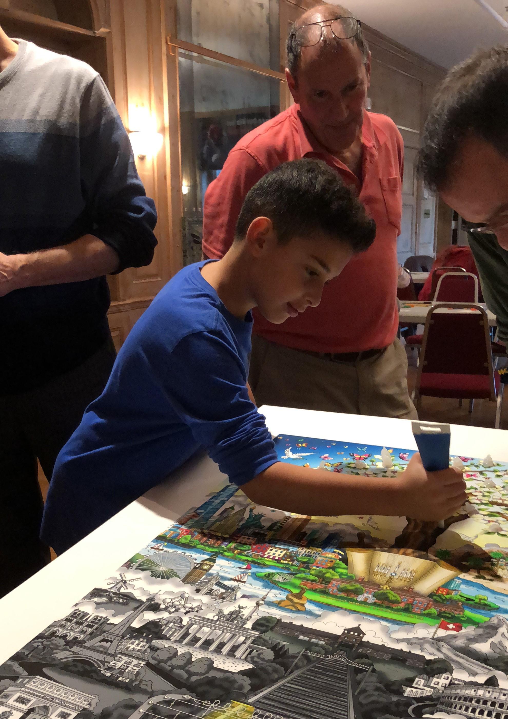 Young boy in a blue shirt adding glue dots to create 3d pop art