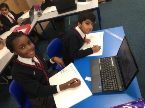 Two kids looking up from doing research on their laptop at the Primary School in the UK