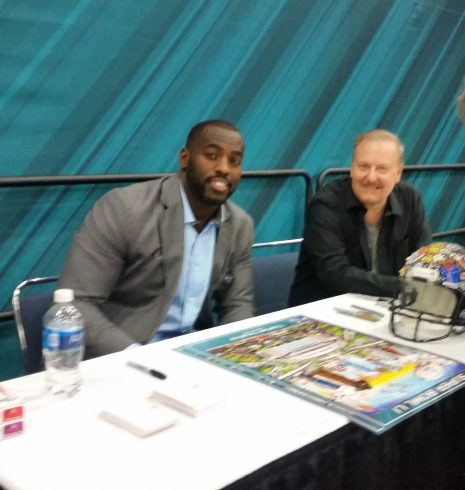 Fazzino and NFL players sit at a table signing posters during the Super Bowl