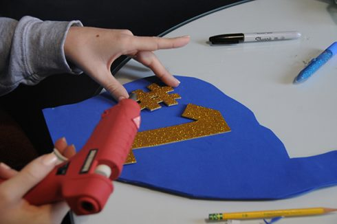 Gluing down a gold sparkly #1 on a foam finger