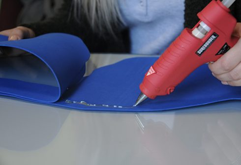 Gluing two pieces of blue foam together with a glue gun