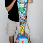 Image of Charles Fazzino standing next to the New Rochelle town installation he created