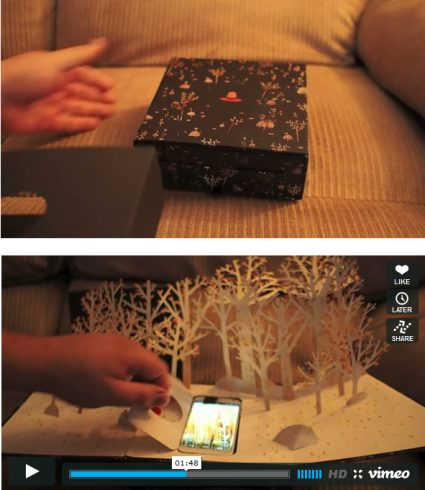 Image of Motorola's pop up book sitting on a coach, following another image with the book opened and a person playing with their phone in the pages