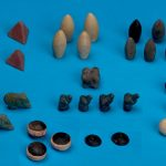 Lying on a board table are several different decorative rocks that are believed to be pieces to an ancient board game