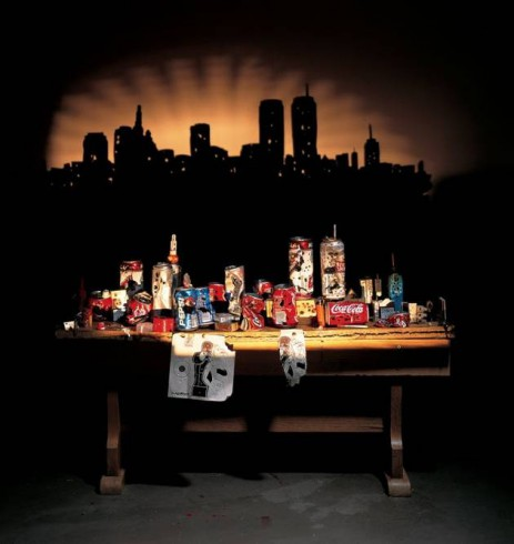 Image garbage arranged on a table so that it casts a shadow of a city skyline