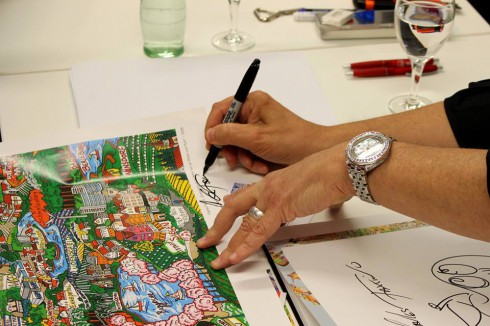 Close up image of Charles Fazzino's hands signing a piece of artwork