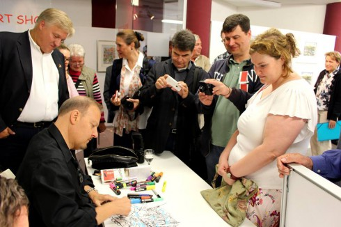 Fazzino surrounded by crowds of fans as he signs a piece of artwork for a young women.
