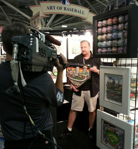 Fazzino standing in front of a video camera ready to be interviewed as he holds up his hand painted home plate.