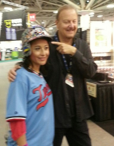 Melissa Colorado wearing a Fazzino hand painted MLB baseball helmet as they pose for a picture.
